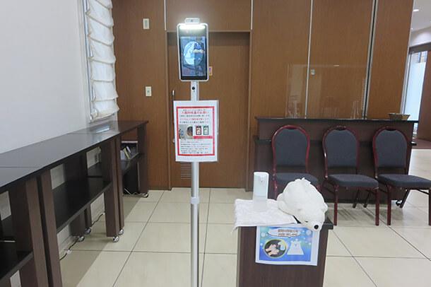 建物エントランスに検温器と消毒剤設置